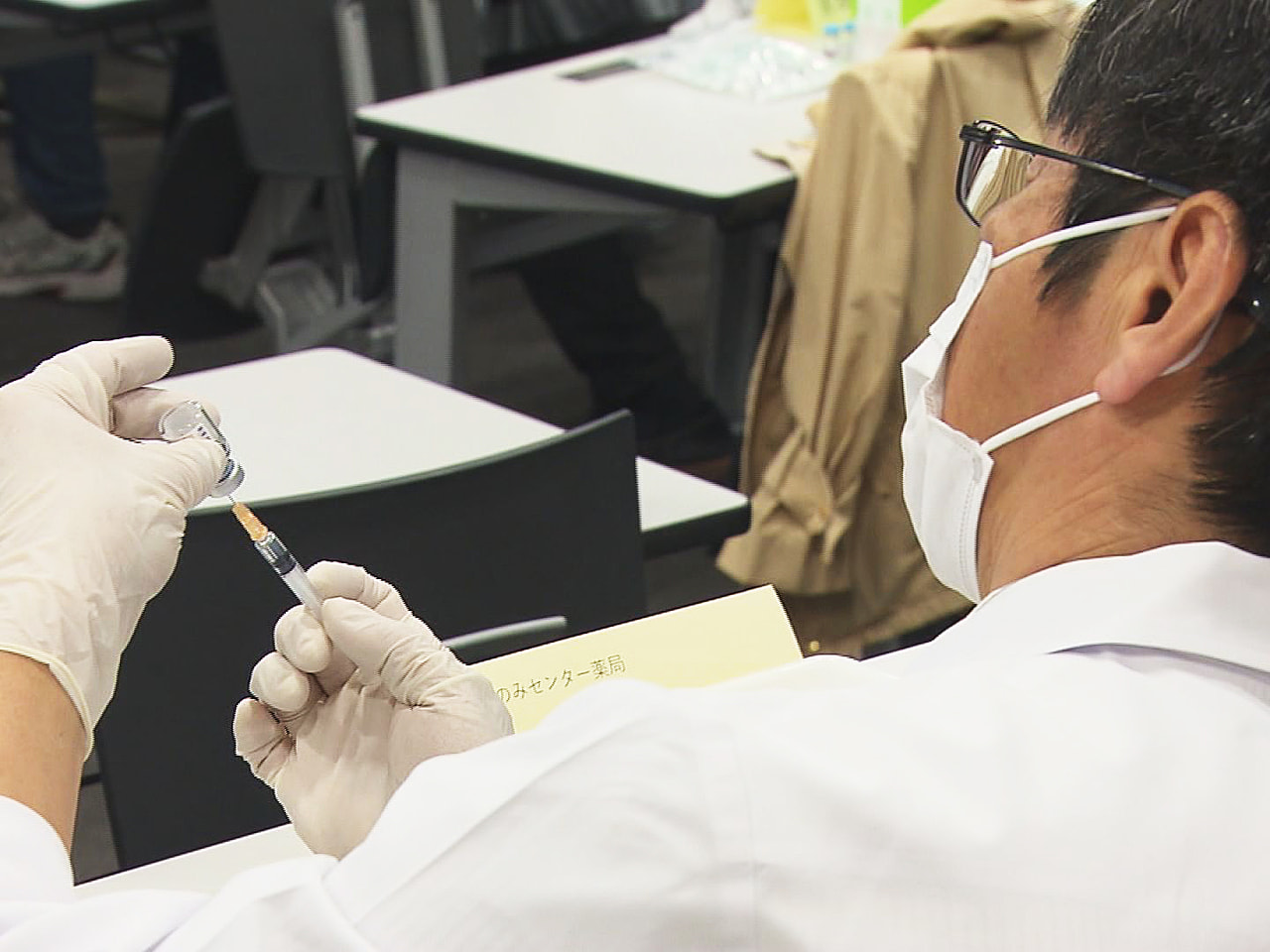 岐阜市の新型コロナウイルスワクチンの集団接種で、調剤して注射器に充てんする薬剤師...