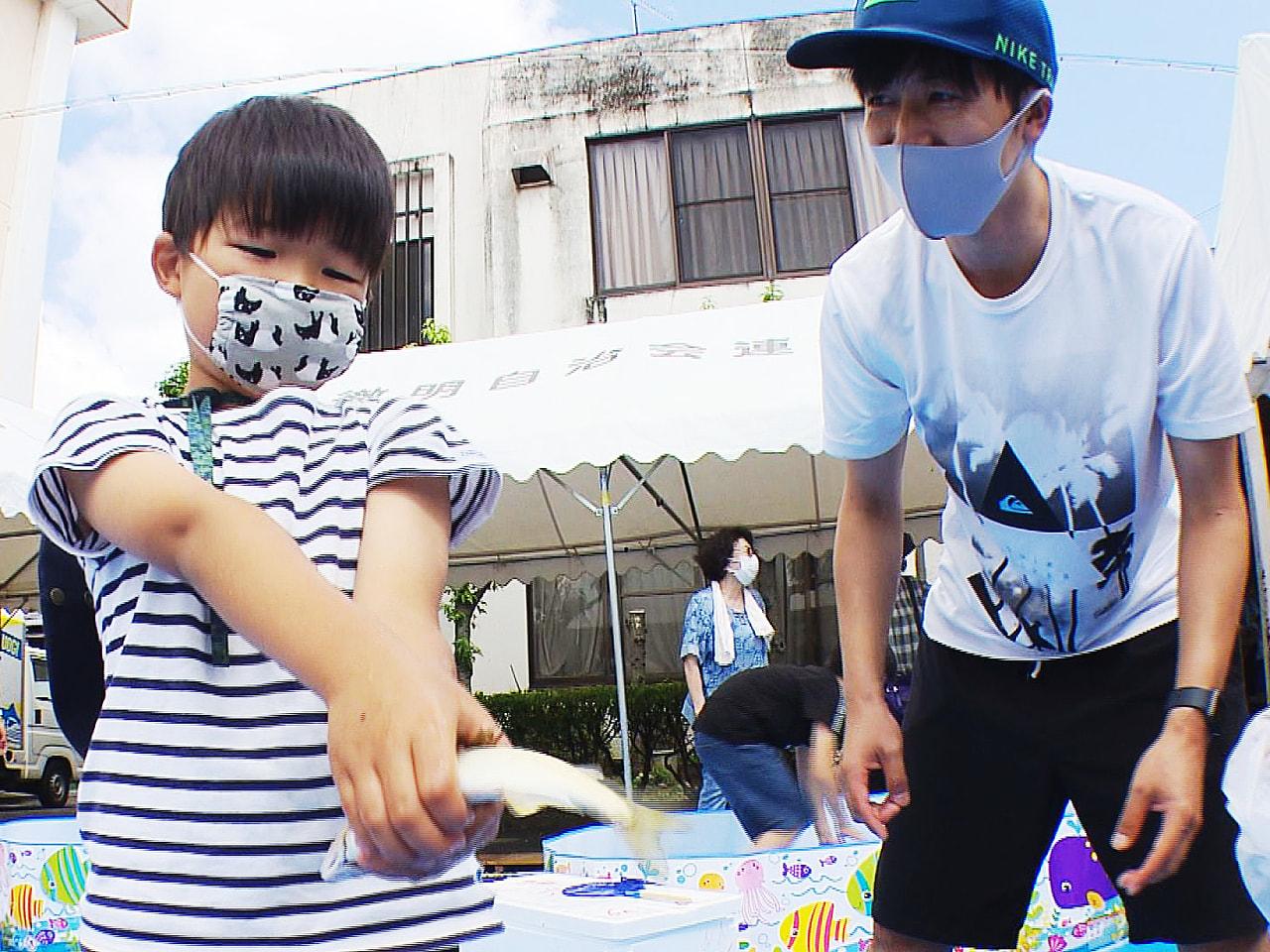 子どもたちが素手でアユを捕まえる「鮎つかみ大会」が岐阜市で開かれ、参加者はプール...